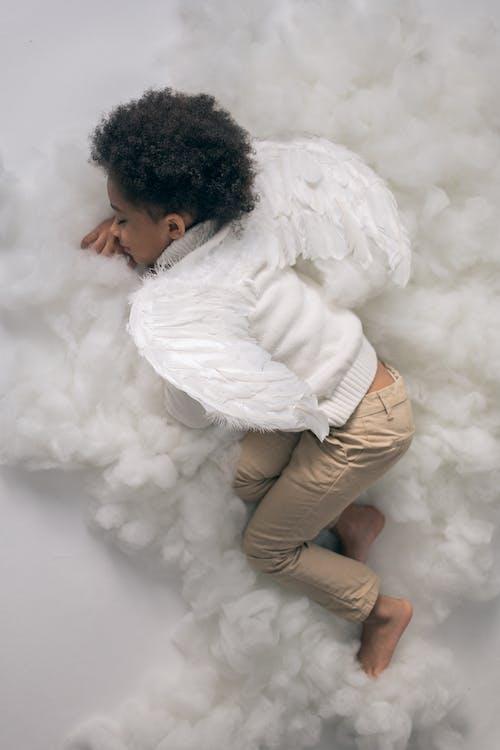 Black boy in wings lying on cotton