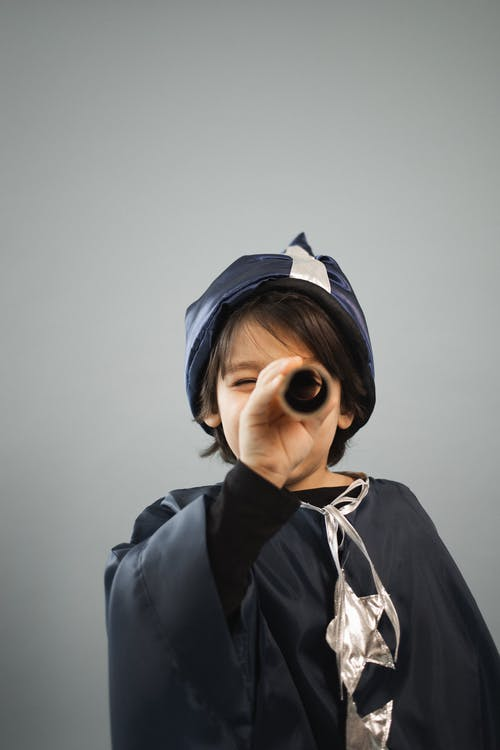 Boy in astrologer costume looking through spyglass