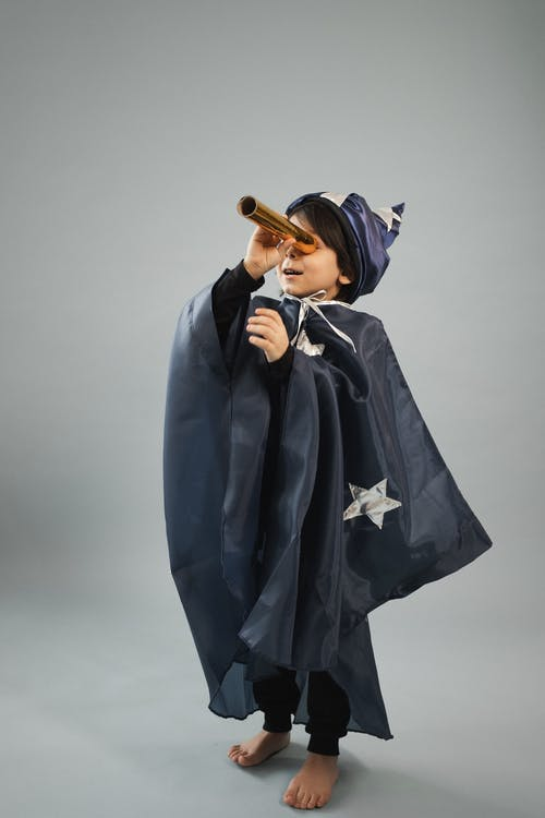 Kid in cape of astronomer and cap looking into toy telescope while standing on gray background
