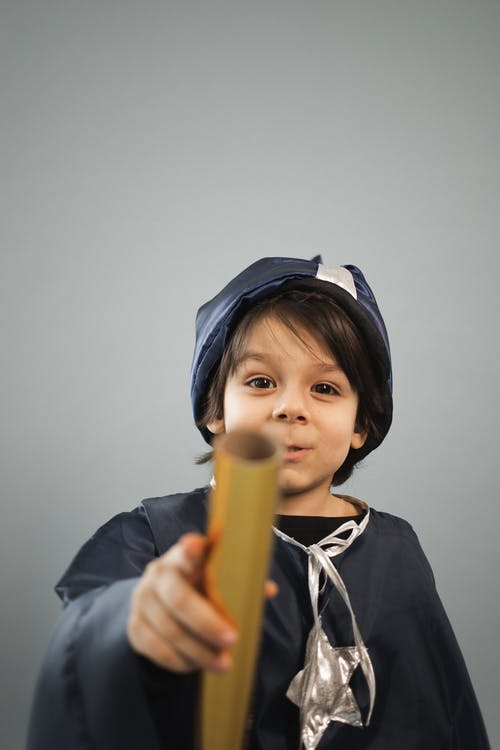 Charming boy in astrologer costume with spyglass