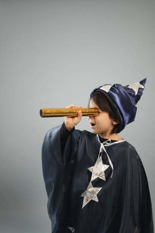 Surprised boy wearing masquerade costume of magician looking through kaleidoscope tube while standing against gray background