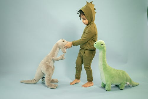 Little black boy with hairstyle playing with toy dinosaur