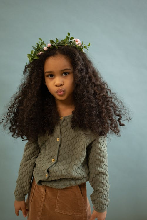 Cute African American girl with curly hair wearing casual wear and wreath standing in studio against blue background and looking at camera