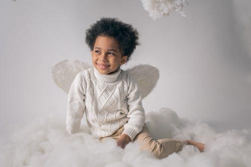 Happy black boy in angel costume on cotton wool
