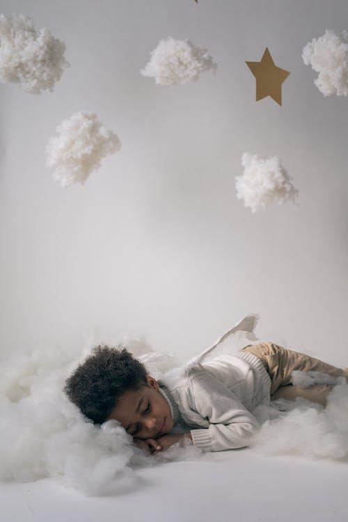 Sleepy black boy in angel costume sleeping in decorated studio