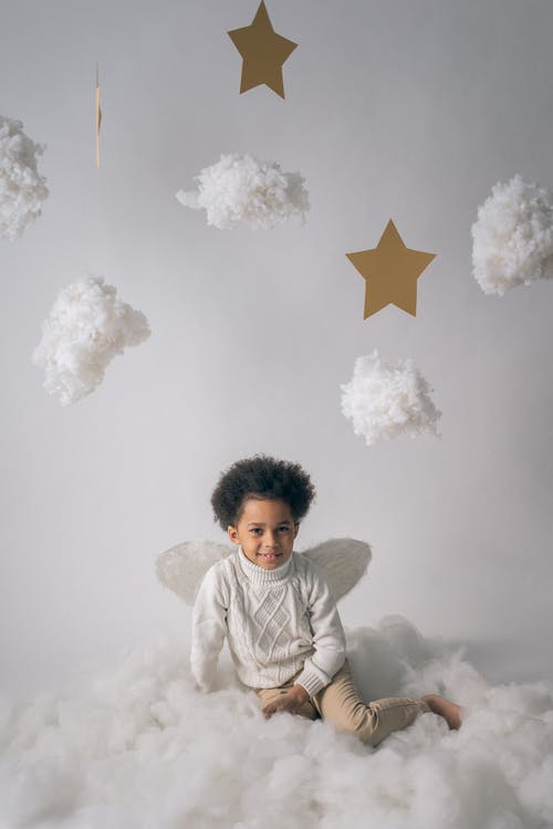 Adorable black boy in angel wings near decorative clouds
