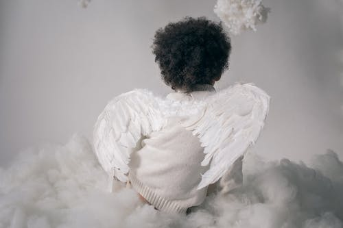 Anonymous boy in angel wings sitting on cotton cloud