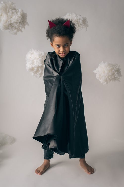 Full body of cute barefoot African American boy wearing devil costume with horns looking at camera on white background in studio