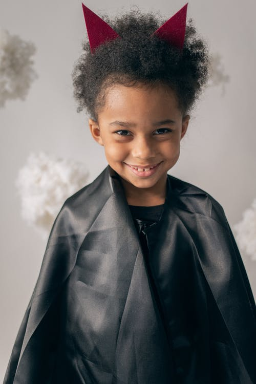 Cheerful African American boy wearing black devil with red horns looking at camera while standing on white background with decorative cotton clouds