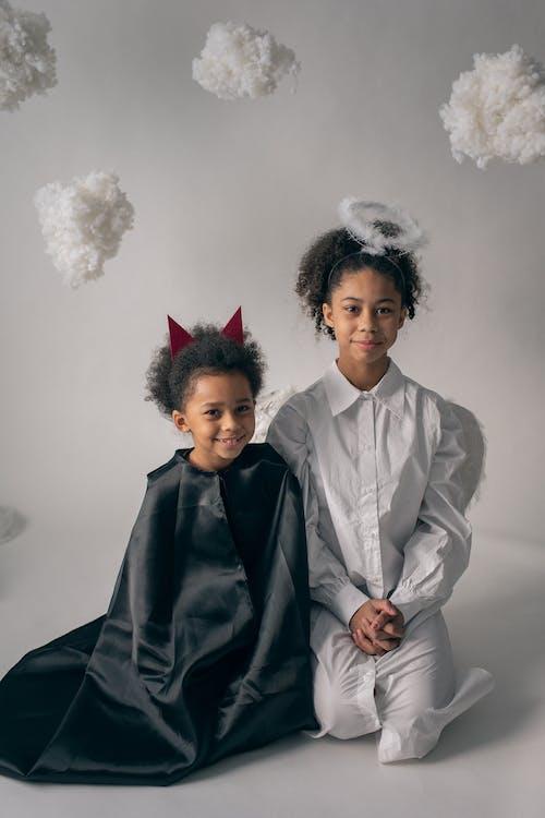 Happy siblings in costumes sitting on floor