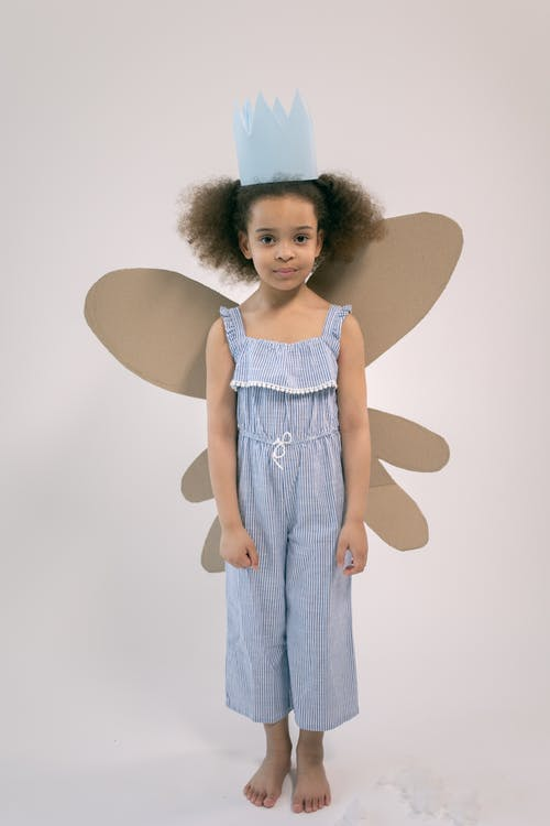Full body of adorable little girl with paper crown and cardboard wings looking at camera and standing on white background in studio