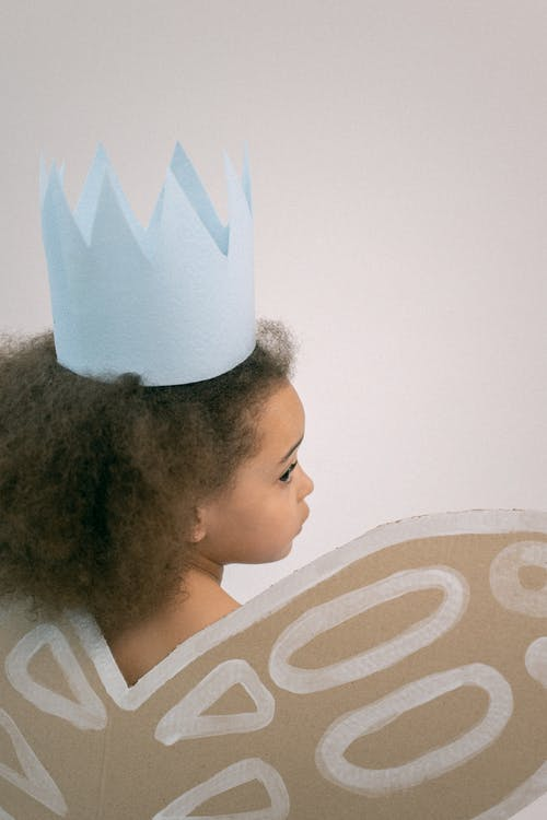 Little girl in paper crown and wings
