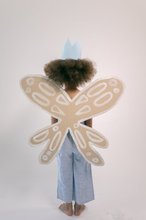Back view full body of little girl with afro wearing blue paper crown and cardboard wings with white pattern while standing in white studio
