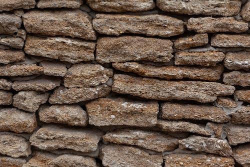 Backdrop of dry stone wall with uneven surface