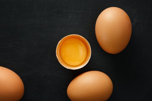 Top view of whole and half of fresh chicken eggs with yolk representing uniqueness concept