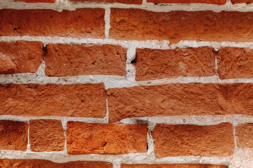 Textured backdrop of bricks between cement layers with uneven surface and dense structure in daytime