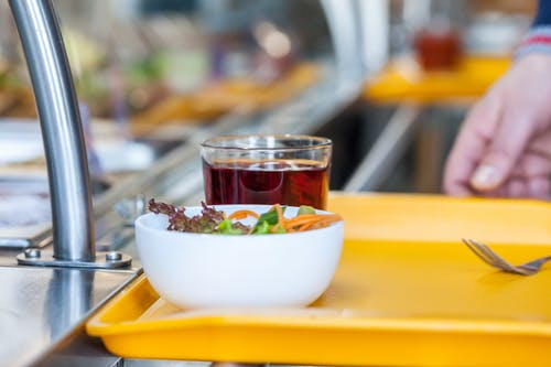 Crop unrecognizable person with bowl of delicious salad and glass of refreshing drink in self service restaurant