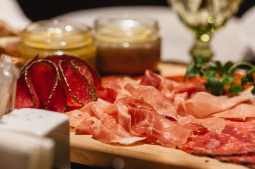 Delicious assorted cured sausage pieces on wooden tray between sauces and salt shaker on blurred background