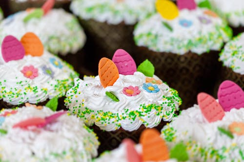 Tasty desserts with whipped meringue cream and sprinkles with colorful decorative eggs on top in confectionery