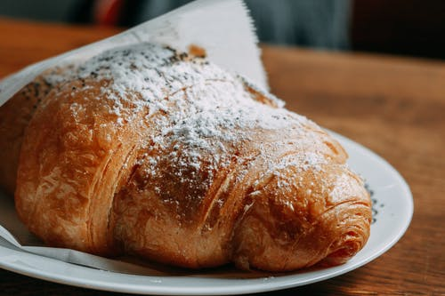 Delicious freshly baked croissant placed on light table on wooden table against blurred background in daytime