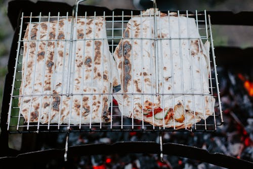 From above of appetizing meat and vegetables in lavash grilling on metal grate in daytime