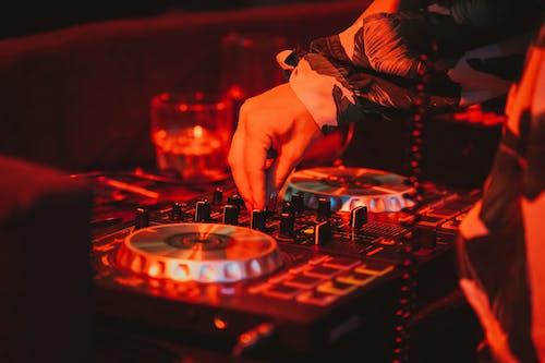 DJ mixing music on remote control in nightclub