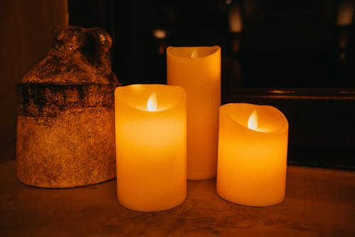 Decorative yellow burning candles placed near aged ceramic vase in dark room against blurred background
