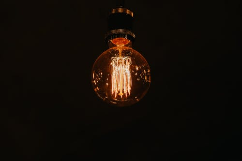 From below of glowing stylish lamp with warm light hanging in dark room