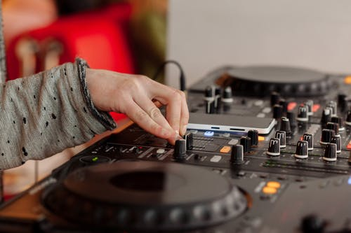 DJ playing music at mixing console