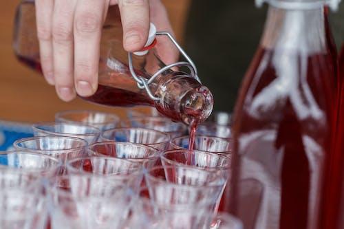Man pouring red lemonade into glassware