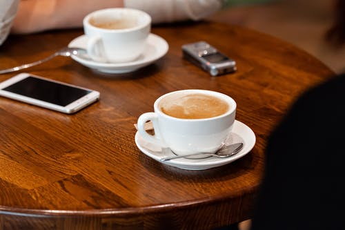 High angle of mugs with latte on saucer with spoon placed on wooden table near phone and voice recorder near crop anonymous person in light cafeteria
