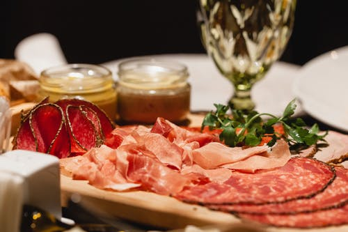 Delicious meat and salami with sauce and wineglass on table