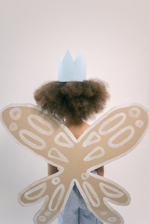 Kid wearing crown and cardboard wings with white pattern