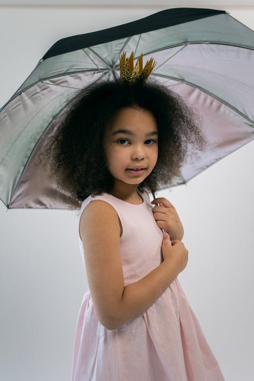 Adorable little African American girl with dark curly hair in trendy pink dress and crown headband standing against white background with umbrella in hand and looking at camera