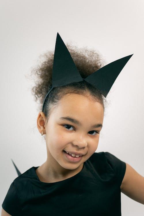 Positive little black child in carnival costume smiling at camera in studio