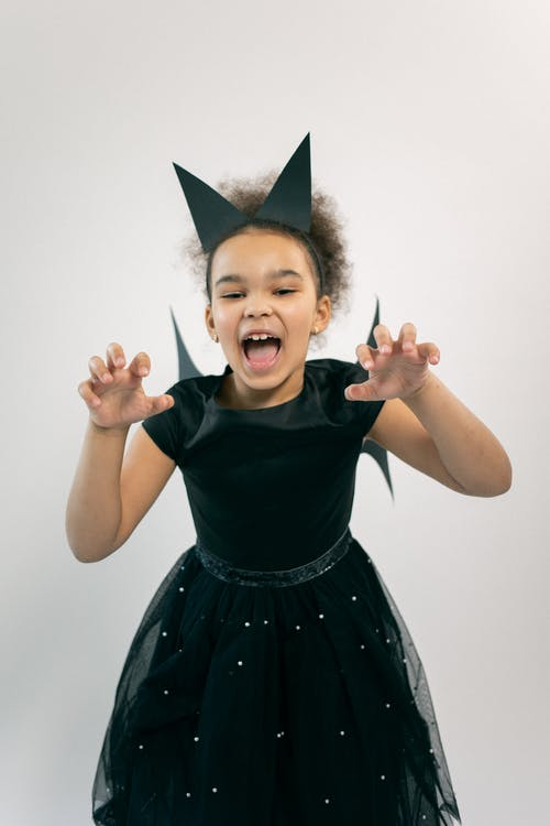 Adorable little ethnic kid showing claws and roaring against white background