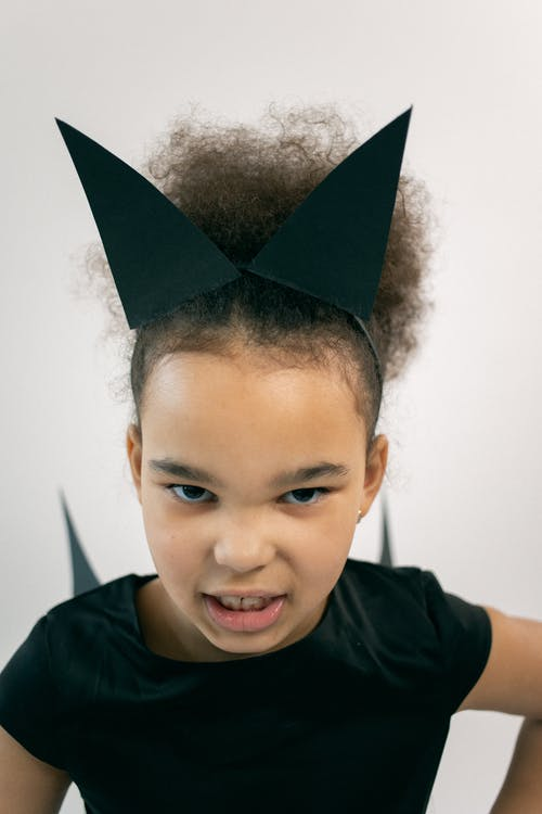 Serious little black girl with Afro hair in Halloween costume and headband gazing at camera and roaring while imitating cat against white background