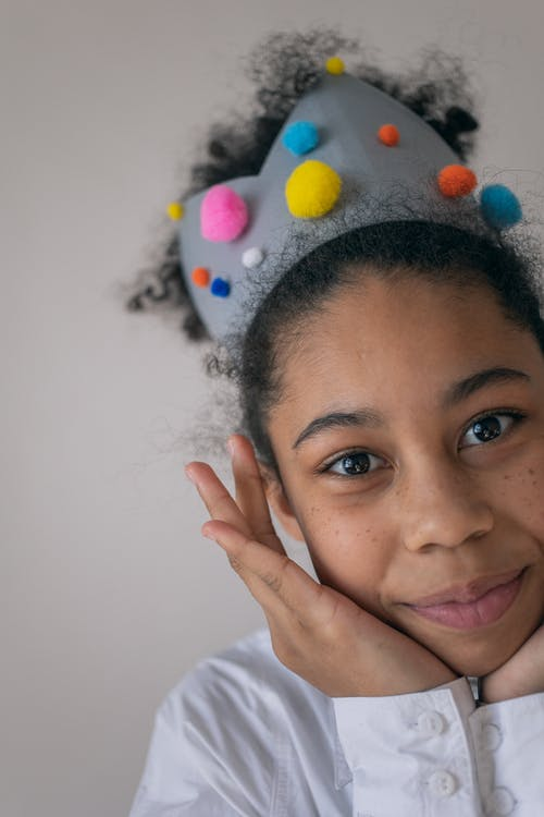Crop happy African American preteen girl with dark curly hair in white shirt and soft crown with colorful pompoms smiling and putting hands on cheeks while looking at camera