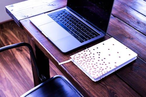 Kostenloses Stock Foto zu laptop und buch, schreibtisch