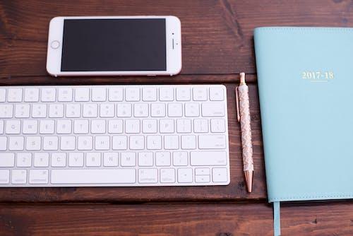 Kostenloses Stock Foto zu handy, kugelschreiber, schreibtisch