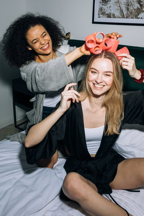 Two Young Women Having Fun Putting Hair Rollers on Their Hair