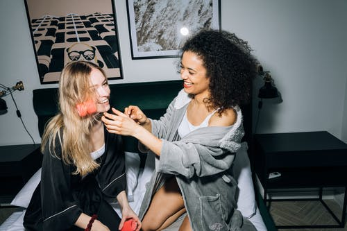 Two Young Women Putting Hair Rollers on Their Hair