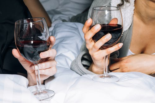 Close-Up View of Two Persons Holding a Wine Glass With Red Wine