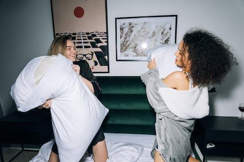 Due Giovani Donne Che Hanno Divertimento Facendo Lotta Con I Cuscini