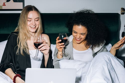 Two Young Women Having Fun While Looking at a Laptop