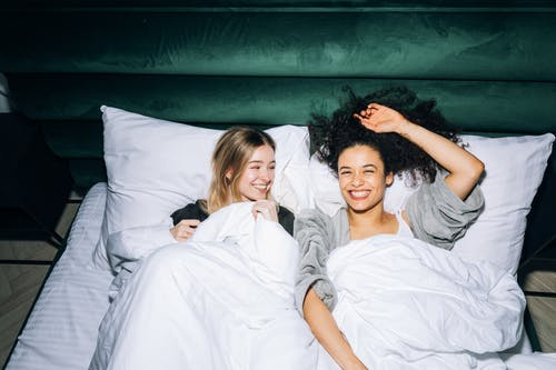 Two Young Women Having Fun While Lying on White Bed