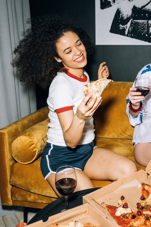 Young Woman Having Fun While Eating Pizza