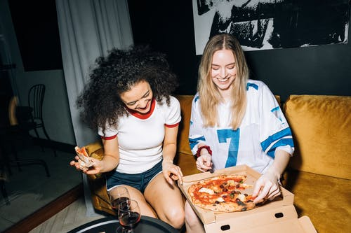 Two Young Women Eating and Getting a Slice of Pizza