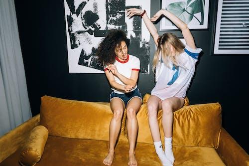 Two Young Women Having Fun While Sitting on a Yellow Sofa