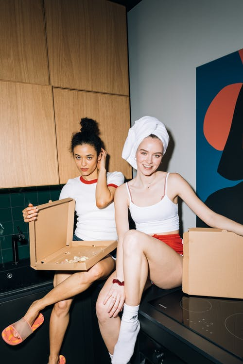 Two Young Women Sitting on a Kitchen Counter